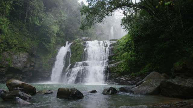 wide slow motion panning shot of waterfall in rain forest / santa juana, costa rica - 瀑布 個影片檔及 b 捲影像