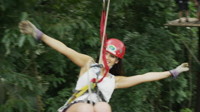 wide slow motion panning shot of woman swinging from zipline in rain forest / quepos, puntarenas, costa rica - ロープスライダー点の映像素材/bロール