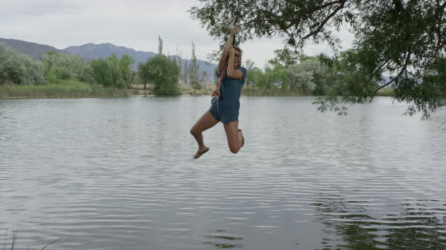 wide slow motion panning shot of woman swinging into lake / mona, utah, united states - rope swing stock videos & royalty-free footage