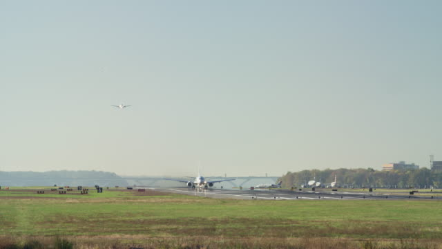 Wide slow motion shot of airplane taking off from runway / Washington D.C., District of Columbia, United States