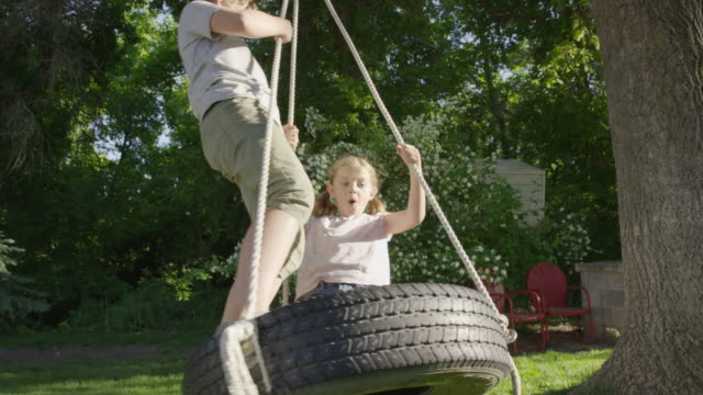 wide slow motion shot of boy and girl on tire swing / springville, utah, united states - springville utah stock videos & royalty-free footage