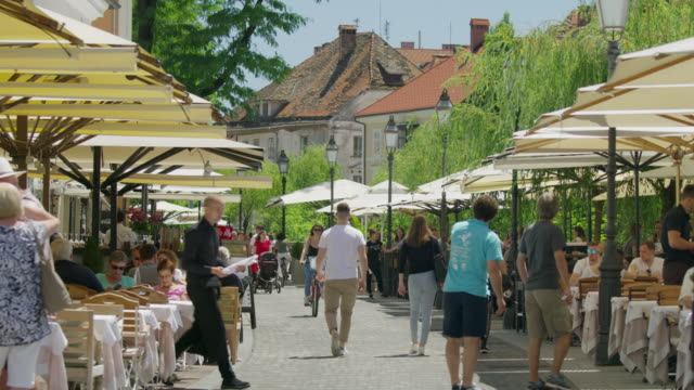 Wide slow motion shot of busy city sidewalk restaurant / Ljubljana, Slovenia