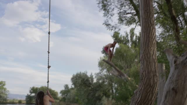 Wide slow motion shot of couple jumping into lake / Mona, Utah, United States