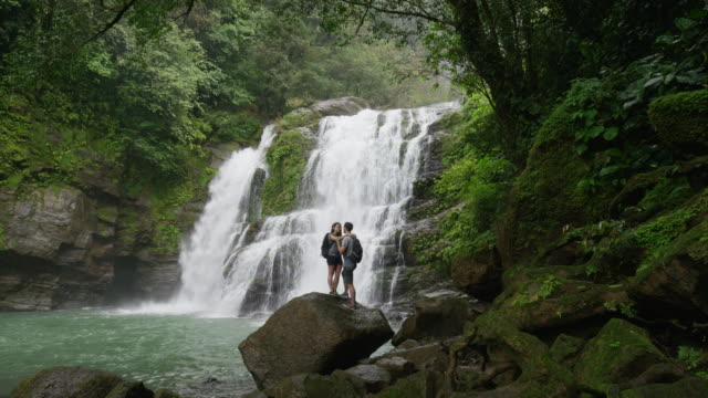 wide slow motion shot of couple kissing near waterfall in rain forest / santa juana, costa rica - wide stock-videos und b-roll-filmmaterial
