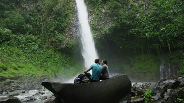 vídeos de stock, filmes e b-roll de wide slow motion shot of couple kissing near waterfall in rain forest / arenal, la fortuna, costa rica - domingo