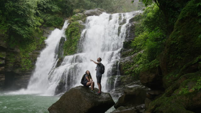 Wide slow motion shot of couple standing near waterfall in rain forest / Santa Juana, Costa Rica