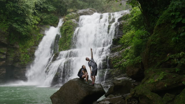 vídeos de stock e filmes b-roll de wide slow motion shot of couple standing near waterfall in rain forest / santa juana, costa rica - costa rica