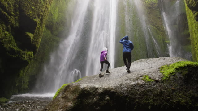 wide slow motion shot of couple standing on rock at bottom of waterfall / rangarvallasysla, iceland - adventure stock videos & royalty-free footage