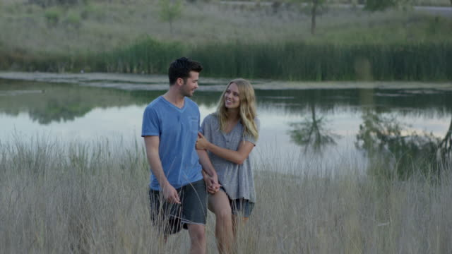 wide slow motion shot of couple walking / mona, utah, united states - zungenkuss stock-videos und b-roll-filmmaterial