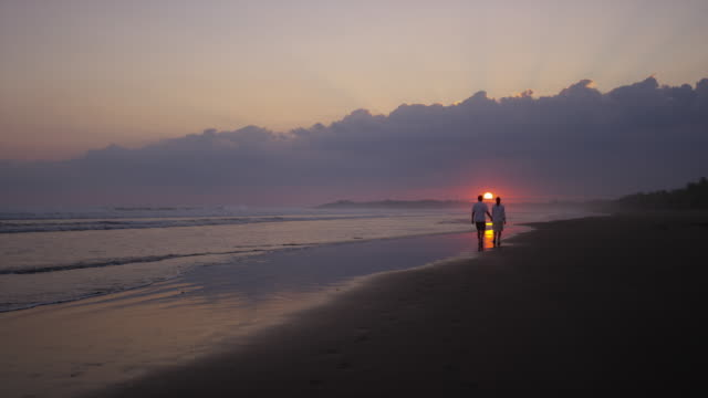 """Wide slow motion shot of couple walking on beach at sunset / Esterillos, Puntarenas, Costa Rica"""