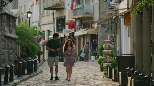 vídeos de stock, filmes e b-roll de wide slow motion shot of couple walking on cobblestone street / veliko tarnovo, bulgaria - bulgária