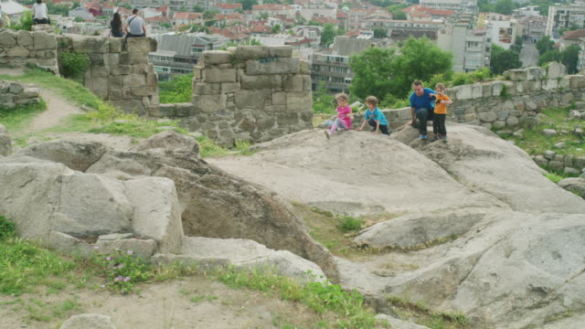 wide slow motion shot of family playing on rocks near city / plovdiv, bulgaria - bulgaria stock videos & royalty-free footage