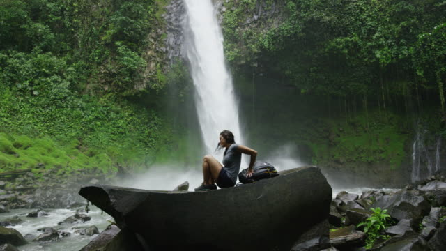 Wide slow motion shot of hiker resting near waterfall in rain forest / Arenal, La Fortuna, Costa Rica