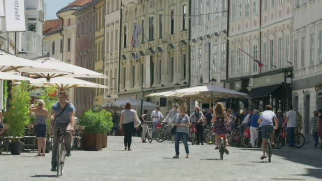 Wide slow motion shot of people in busy plaza / Ljubljana, Slovenia
