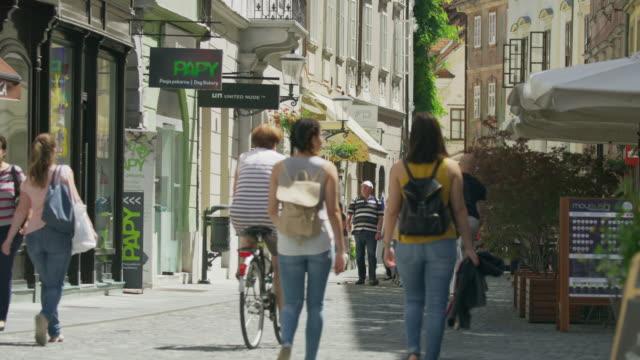 Wide slow motion shot of people walking in city / Ljubljana, Slovenia