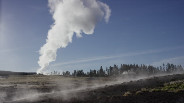 stockvideo's en b-roll-footage met wide slow motion shot of smoking geyser in remote landscape / yellowstone national park, wyoming, united states - old faithful geiser