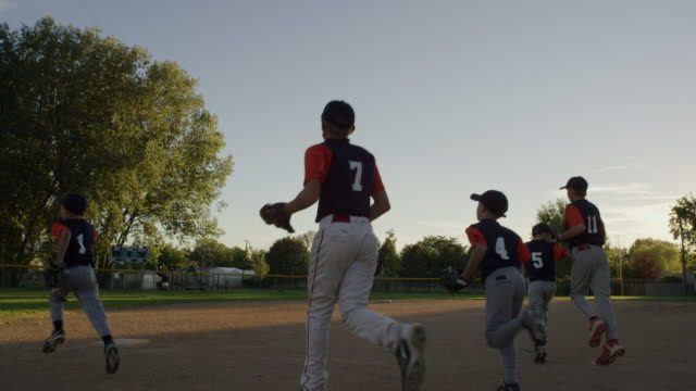 Wide slow motion shot of team running on baseball field / American Fork, Utah, United States