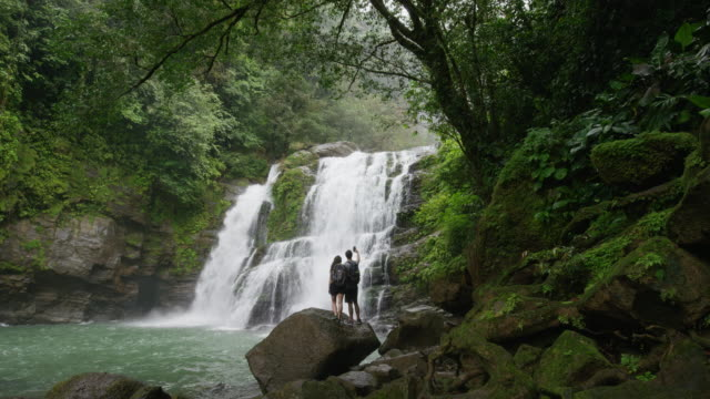 Wide slow motion shot of tourists photographing waterfall in rain forest / Santa Juana, Costa Rica