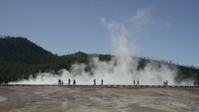 Wide slow motion shot of tourists visiting steaming geyser / Yellowstone National Park, Wyoming, United States