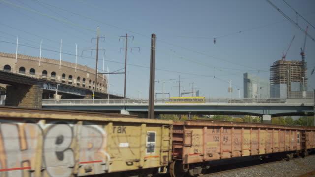 wide slow motion shot of train in train yard / new york, new york, united states - 操車場点の映像素材/bロール