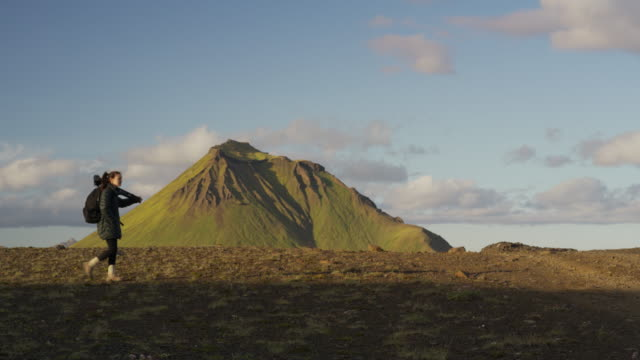 Wide slow motion shot of woman carrying tripod in mountain landscape / Rangarvallasysla, Iceland