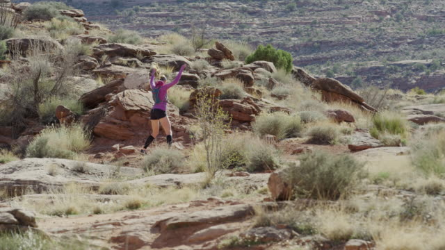 vídeos de stock e filmes b-roll de wide slow motion shot of woman doing jumping jacks in desert / moab, utah, united states - gola alta