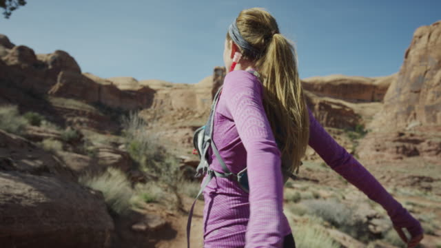 wide slow motion shot of woman stretching then trail running in desert / moab, utah, united states - rucksack stock-videos und b-roll-filmmaterial
