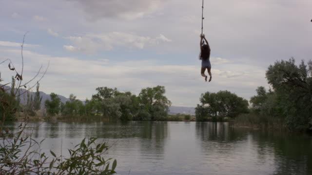 Wide slow motion shot of woman swinging into lake / Mona, Utah, United States