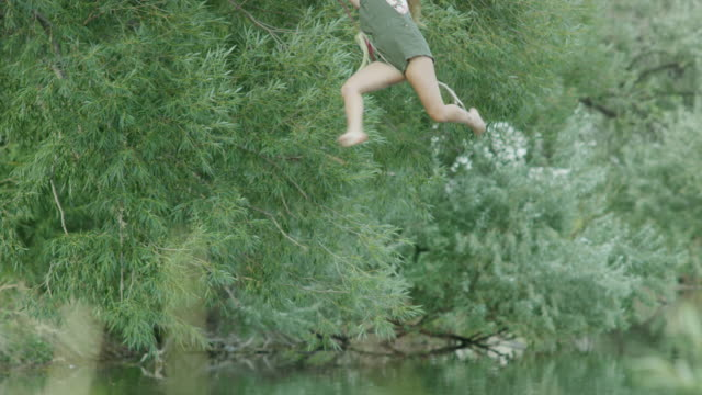 wide slow motion shot of woman swinging into lake / mona, utah, united states - swinging stock videos and b-roll footage