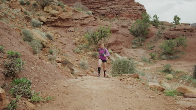 Wide slow motion shot of woman trail running in desert / Fisher Towers, Utah, United States