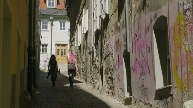 vidéos et rushes de wide slow motion shot of women walking in alley / ljubljana, slovenia - ljubljana