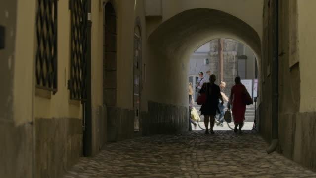 Wide slow motion shot of women walking in tunnel toward street / Ljubljana, Slovenia
