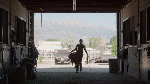 wide slow motion silhouette of girl carrying saddle and rope into stable / lehi, utah, united states - lehi stock videos & royalty-free footage