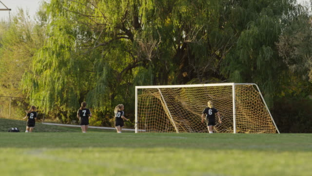 wide slow motion surface level shot of soccer players practicing / springville, utah, united states - grandangolo tecnica fotografica video stock e b–roll
