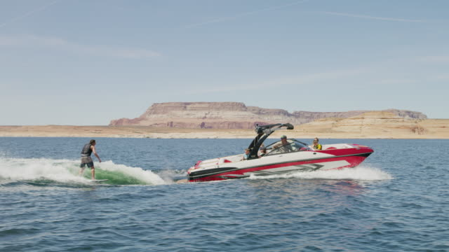 wide slow motion tracking shot of boat pulling wake surfer / lake powell, utah, united states - lake powell stock videos & royalty-free footage