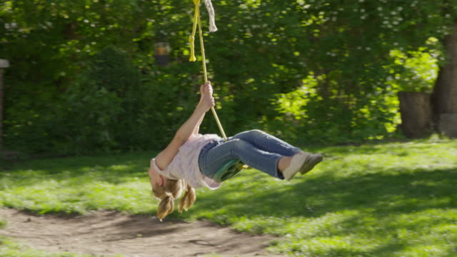 wide slow motion tracking shot of boy pushing girl on rope swing / springville, utah, united states - springville utah stock-videos und b-roll-filmmaterial