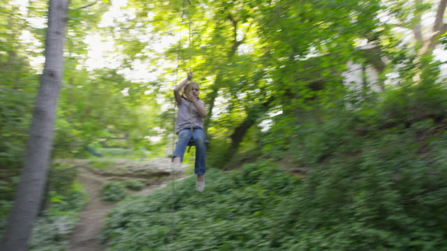 wide slow motion tracking shot of boy swinging on rope swing / springville, utah, united states - springville utah stock videos & royalty-free footage