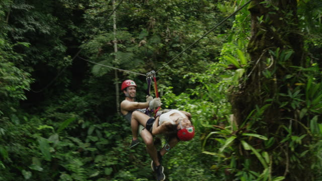 Wide slow motion tracking shot of couple on ziplining in rain forest / Quepos, Puntarenas, Costa Rica