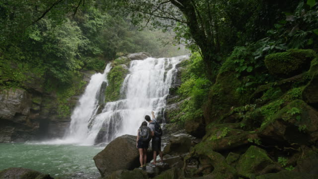 wide slow motion zoom in of couple admiring waterfall in rain forest / santa juana, , costa rica - costa rica stock videos and b-roll footage
