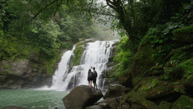 vidéos et rushes de wide slow motion zoom out of couple admiring waterfall in rain forest / santa juana, , costa rica - zoom out