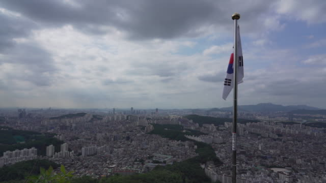 wide, south korea flag overlooks seoul cityscape - south korean flag stock videos & royalty-free footage