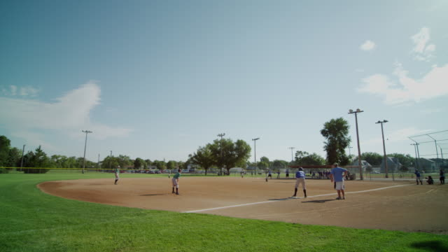 vídeos y material grabado en eventos de stock de wide tableau featuring little league baseball practice at a small town baseball field. batter hits the ball and it is caught in the outfield. - batear