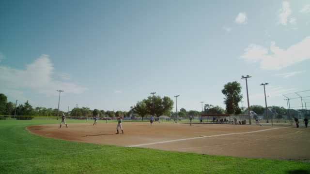 Wide tableau featuring little league baseball practice at a small town baseball field. Runner is safe at third base.