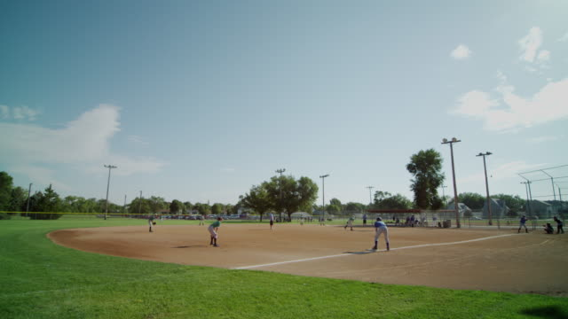 Wide tableau featuring little league baseball practice at a small town baseball field. Batter hits a triple to the right outfield and players round the bases.
