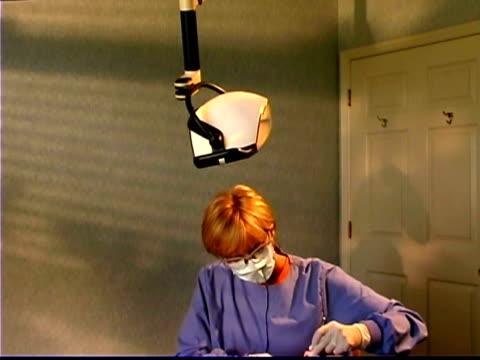 wide tilt down of a dental hygienist checking a patient's teeth. - only mature women stock videos & royalty-free footage