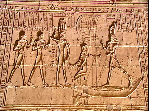 wide tilt down showing the carved reliefs of figures some are standing in boats animals and hieroglyphs on the back wall of the temple of edfu in... - cleopatra stock videos & royalty-free footage