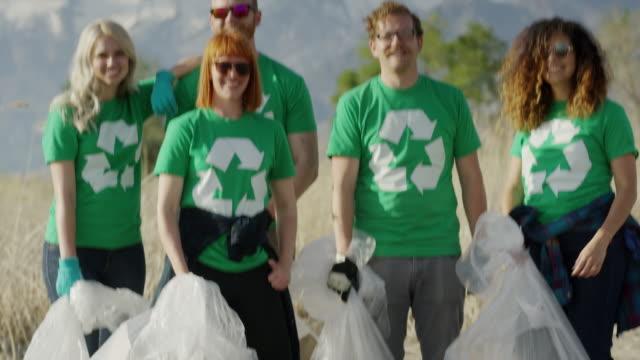 Wide tilt up shot of proud volunteers posing with garbage at beach / Vineyard, Utah, United States