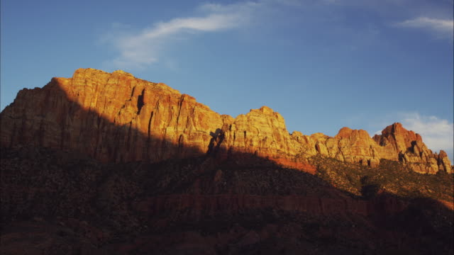 Wide time lapse shot of sun passing over mountain / Zions National Park, Utah, United States