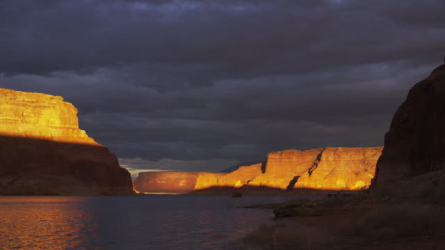 wide time lapse shot of sunrise over rock formations / lake powell, utah, united states - lake powell stock videos & royalty-free footage