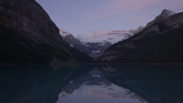 Wide time lapse shot of sunrise over still mountain lake / Lake Louise, Alberta, Canada